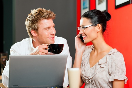 Couple in coffeeshop with laptop and mobile; obviously they are flirting photo