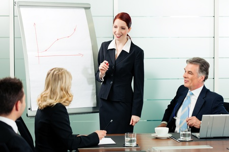 present presentation: Business - presentation within a team; a female colleague is standing on the flipchart Stock Photo