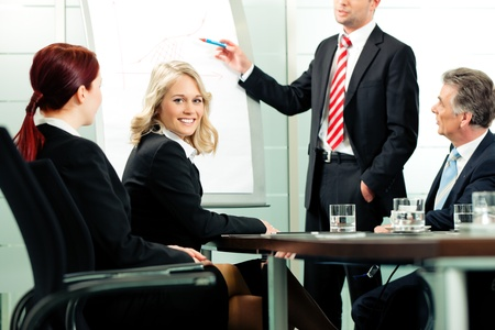 Business - presentation within a team; a colleague is standing on the flipchart photo