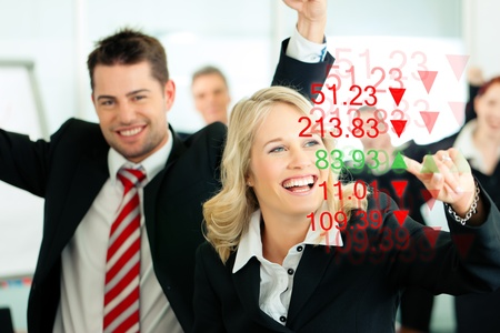 share prices: Business - presentation within a team; a female banker or consultant shows figures or share prices on screen