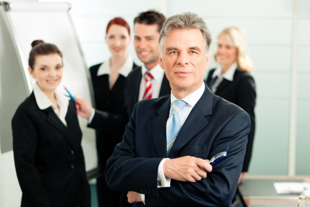 Business - team in an office; the senior executive is standing in front Stock Photo - 9860679