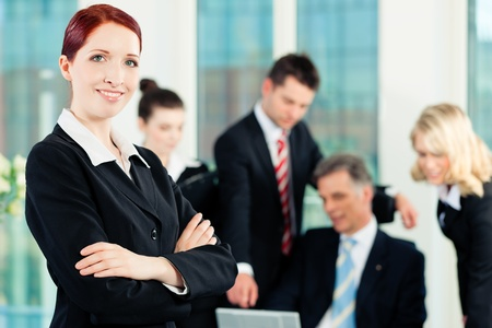 Business - meeting in an office; a colleague is looking into the camera Stock Photo - 9844601