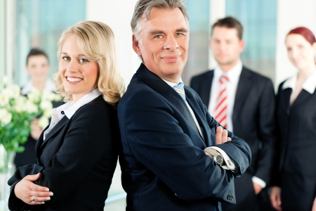 Business - team in an office; the senior executive is standing in front with his secretary photo
