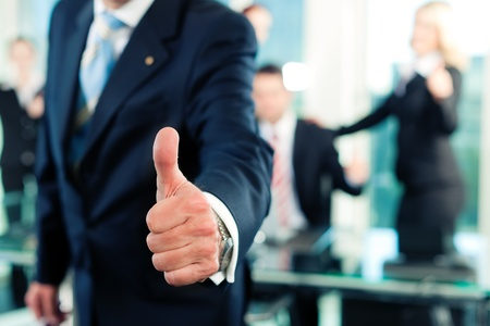 business advice: Business - team in an office; the senior executive has the thumb up; focus on thumb