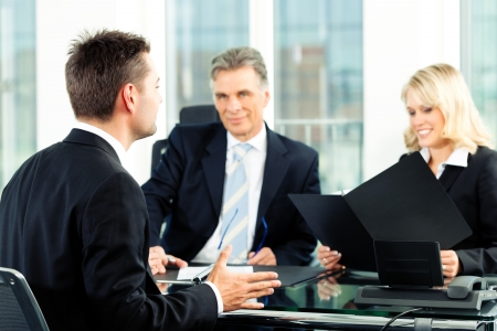 interviewing: Business - young man sitting in job Interview Stock Photo