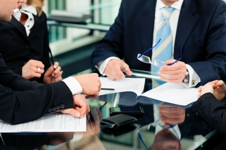 law business: Business - meeting in an office; lawyers or attorneys discussing a document or contract agreement