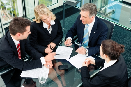 negotiation business: Business - meeting in an office; the businesspeople are discussing a document