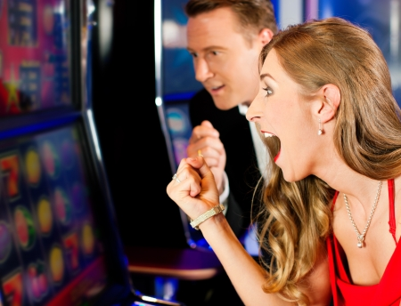 Happy couple in Casino on a slot machine winning Stock Photo - 9844606