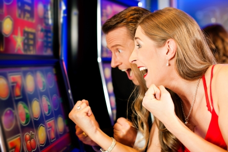 casinos: Happy Couple in Casino on a slot machine winning