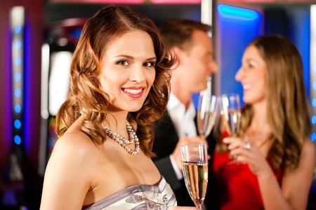 Three friends with champagne in a bar or casino Stock Photo - 9860692