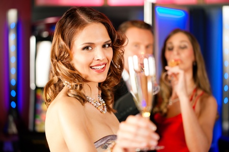 Three friends with champagne in a bar or casino Stock Photo - 9860575