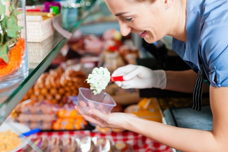 speciality: Working in a butchers shop - a shop assistant with curd cheese Stock Photo