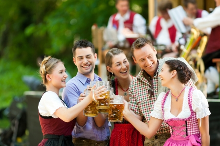 beer glass: In Beer garden in Bavaria, Germany - friends in Tracht, Dirndl and Lederhosen and Dirndl standing in front of band