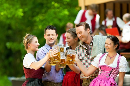 beer mug: In Beer garden in Bavaria, Germany - friends in Tracht, Dirndl and Lederhosen and Dirndl standing in front of band