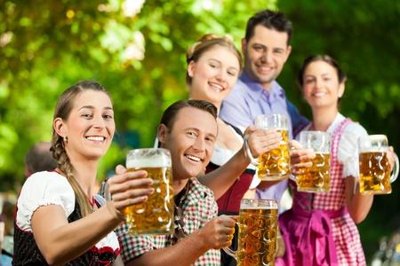 In Beer garden - friends in Tracht, Dirndl and Lederhosen drinking a fresh beer in Bavaria, Germany photo