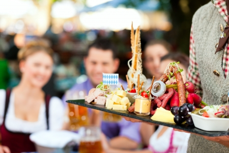 In Beer garden in Bavaria, Germany - beer and snacks are served; focus on meal photo