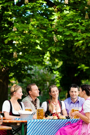 In Beer garden - friends Tracht, Dirndl and on a table with beer and snacks in Bavaria, Germany photo