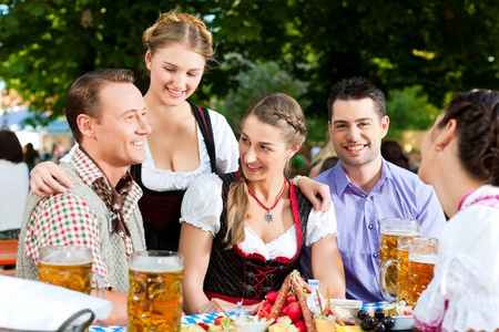 In Beer garden - friends Tracht, Dirndl and on a table with beer and snacks in Bavaria, Germany Stock Photo - 9860902