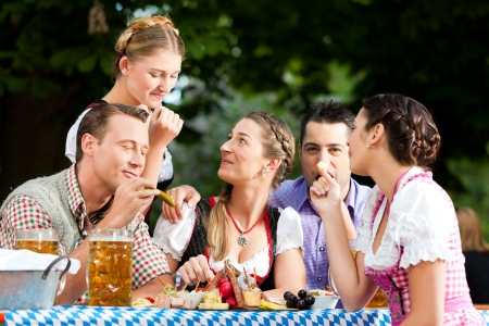 tracht: In Beer garden - friends Tracht, Dirndl and on a table with beer and snacks in Bavaria, Germany Stock Photo