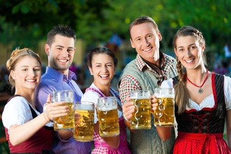 In Beer garden - friends in Tracht, Dirndl and Lederhosen drinking a fresh beer in Bavaria, Germany photo