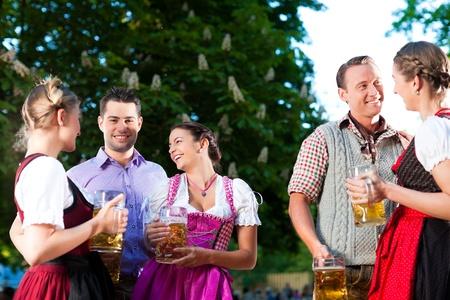 lederhosen: In Beer garden - friends in Tracht, Dirndl and Lederhosen drinking a fresh beer and talk in Bavaria, Germany Stock Photo