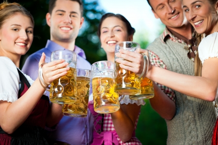 tracht: In Beer garden - friends in Tracht, Dirndl and Lederhosen drinking a fresh beer in Bavaria, Germany