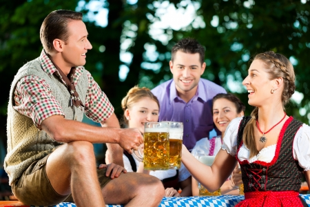 In Beer garden - friends in Lederhosen drinking a fresh beer in Bavaria, Germany