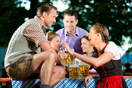 In Beer garden - friends in Lederhosen drinking a fresh beer in Bavaria, Germany Stock Photo - 9860871
