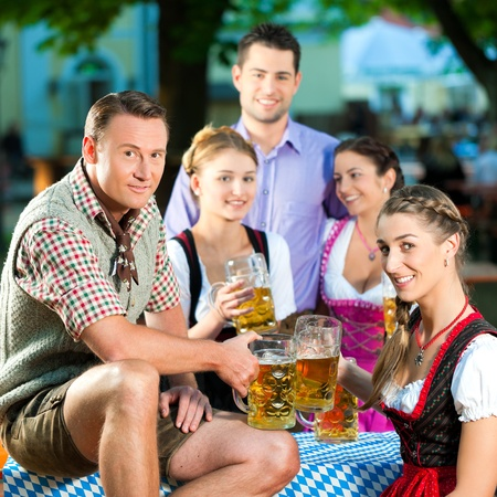 In Beer garden - friends in Lederhosen drinking a fresh beer in Bavaria, Germany photo
