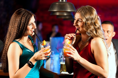 Group of party people with cocktails in a bar or club having fun   photo