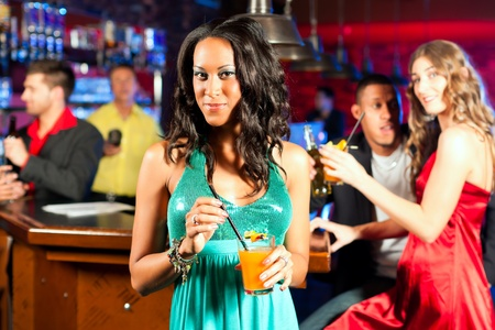 flirt: Group of party people with cocktails in a bar or club having fun; one woman is looking into the camera