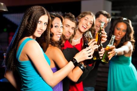 man drinkt bier: Groep mensen - twee vrienden - partij met cocktails in een bar of club plezier