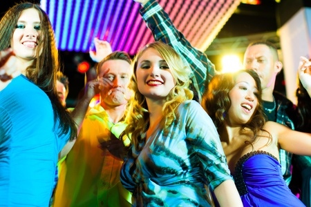 Group of party people - men and women - dancing in a disco club to the music Stock Photo - 9860636