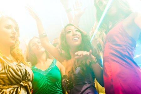 Group of party people - men and women - dancing in a disco club to the music photo