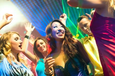 night club: Grupo de parte de personas - hombres y mujeres - bailando en un discoteca club a la m�sica