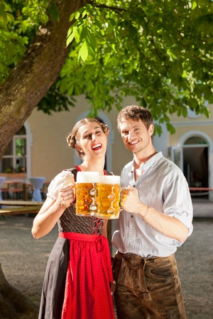 Couple with beer stein and traditional clothes in a beer garden photo