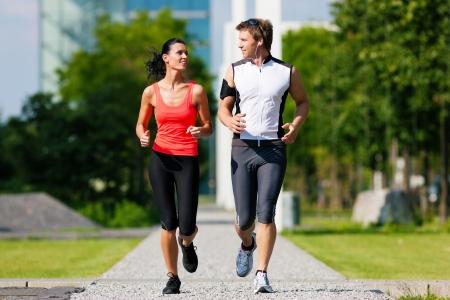 アスリート: 都市スポーツ - カップルの美しい夏の日、市内でフィットネスのジョギング