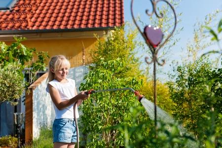 garden hose: Happy child watering flowers in the garden in front of her home
