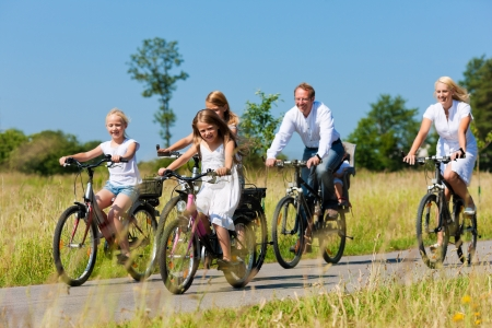 Family with baby and girl child having a weekend excursion on their bikes on a summer day in beautiful landscape photo