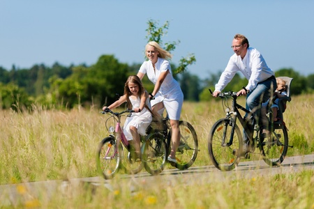 biking: Family with baby and girl child having a weekend excursion on their bikes on a summer day in beautiful landscape Stock Photo