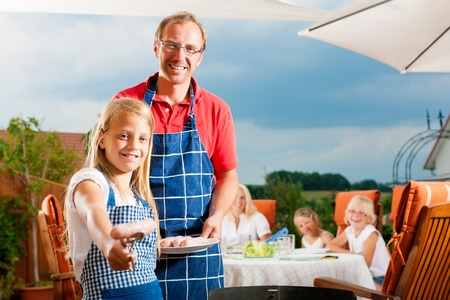 famiglia in giardino: Famiglia felice di avere un barbecue in estate; il padre e un figlio in piedi alla griglia