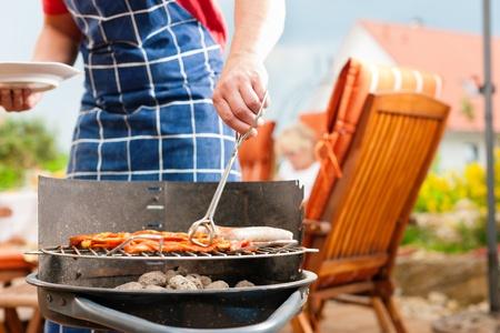 barbecue: Heureuse famille ayant un barbecue en �t� ; p�re se trouve � c�t� du feu Banque d'images