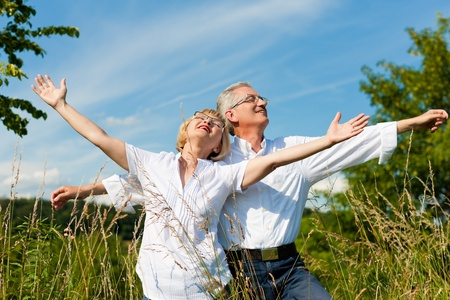 Happy mature couple - senior people (man and woman) already retired - having fun in summer in nature Stock Photo - 9860951