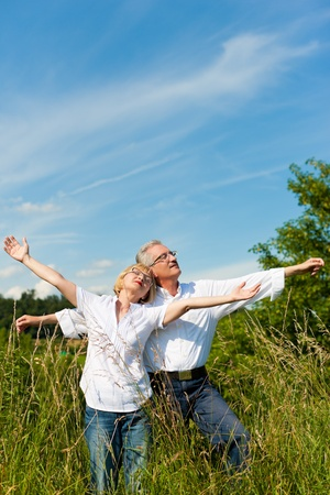 Happy mature couple - senior people (man and woman) already retired - having fun in summer in nature Stock Photo - 9860250