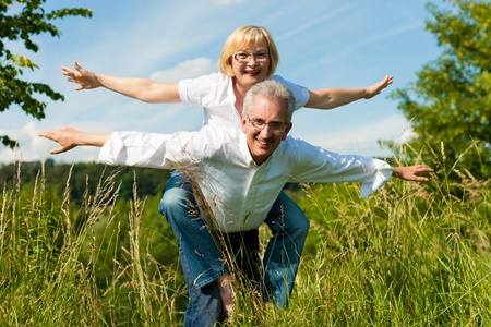 retirees: Happy mature couple - senior people (man and woman) already retired - having fun in summer in nature Stock Photo