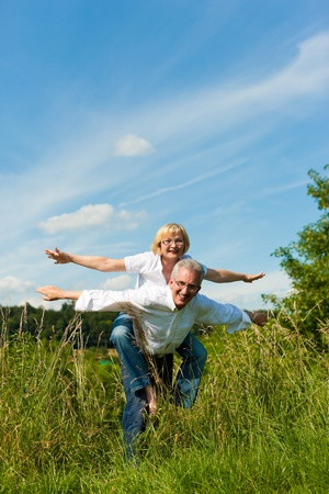 trust people: Happy mature couple - senior people (man and woman) already retired - having fun in summer in nature Stock Photo