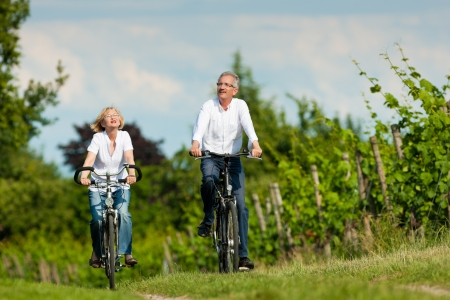 pensioner: Happy mature couple - senior people, man and woman, already retired - cycling in summer in nature