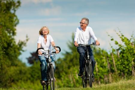 Felice Coppia - persone anziane, l'uomo e la donna, già in pensione - Ciclismo d'estate nella natura