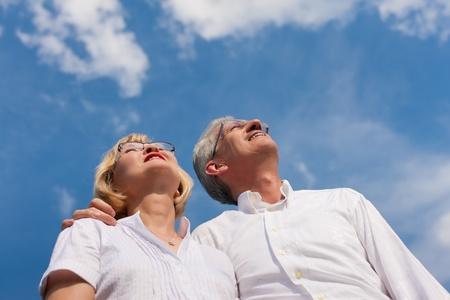pareja madura feliz: Feliz pareja madura - senior personas (hombre y mujer) ya retiradas - mirando al cielo azul en verano