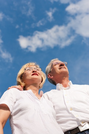 Happy mature couple - senior people (man and woman) already retired - looking to the blue sky in summer Stock Photo - 9860792